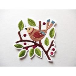 Oiseau dans une branche avec boules rouges